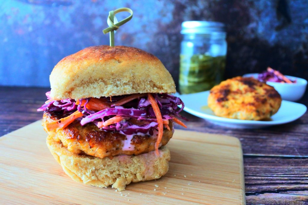 A close up image of a chicken burger topped with a slaw on a wooden board with dishes of patties, slaw and a jar of pickles in the background