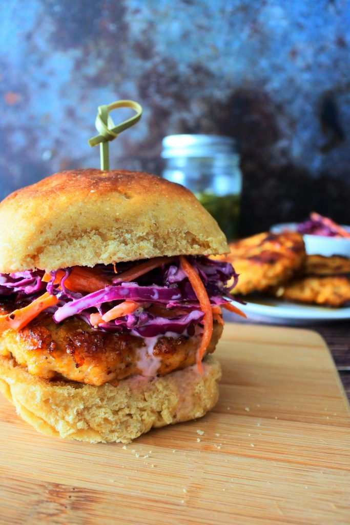 A close up image of a chicken burger topped with a slaw on a wooden board