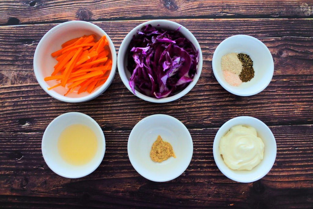 An overhead image of bowls of ingredients for a simple slaw including carrots, red cabbage, spices, mayonnaise, stone ground mustard and lemon juice