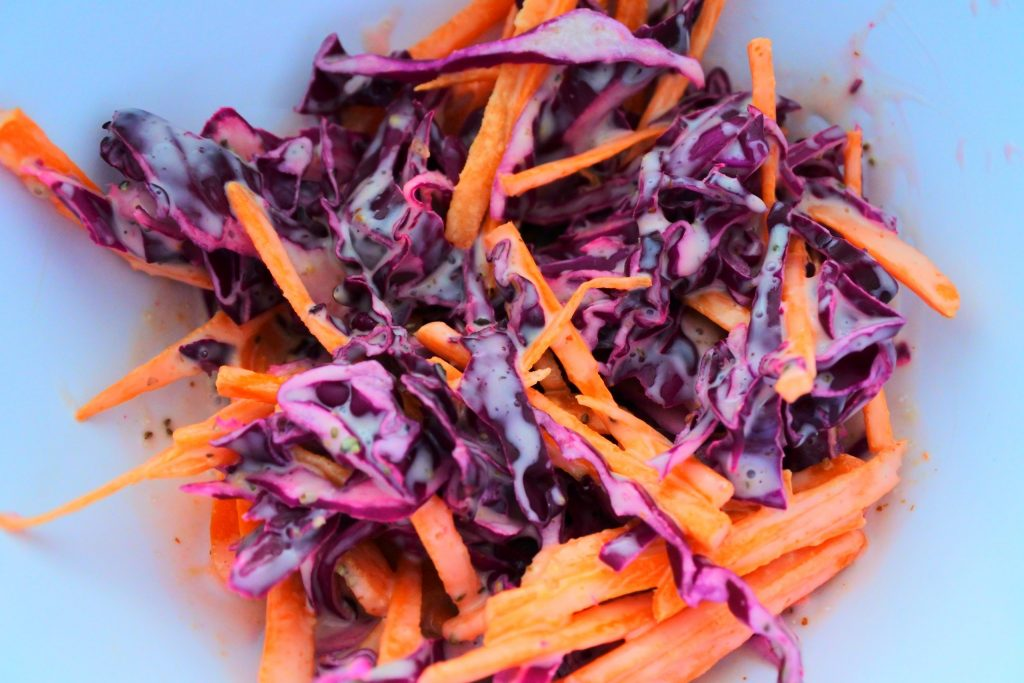 A close up image of a red cabbage and carrot slaw