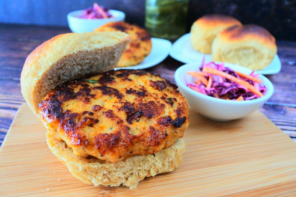 A close up image of a chicken burger on a wooden board with a small dish of slaw next to it.