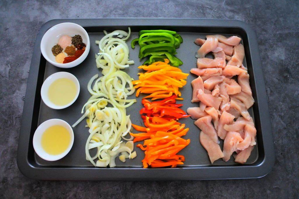 An overhead image of a sheet tray with a row of raw chicken pieces, a row of multicolored bell peppers, a row of sliced onions and a row of small bowls containing lemon juice, light olive oil and a spice blend