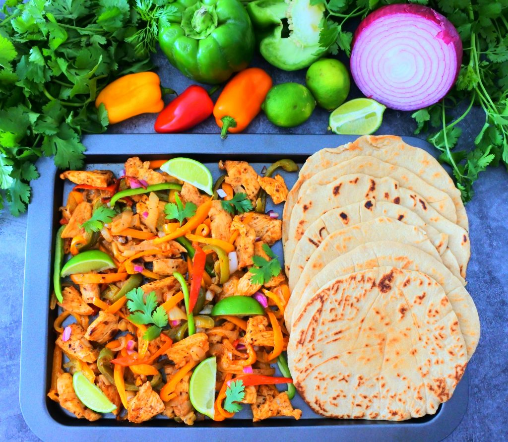 An overhead image of cooked chicken fajitas next to a row of soft and fluffy whole wheat tortillas on a sheet tray with an assortment of fresh veggies to the top border
