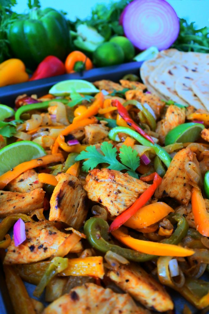An image of cooked chicken fajitas next to a row of soft and fluffy whole wheat tortillas with an assortment of fresh veggies in the background