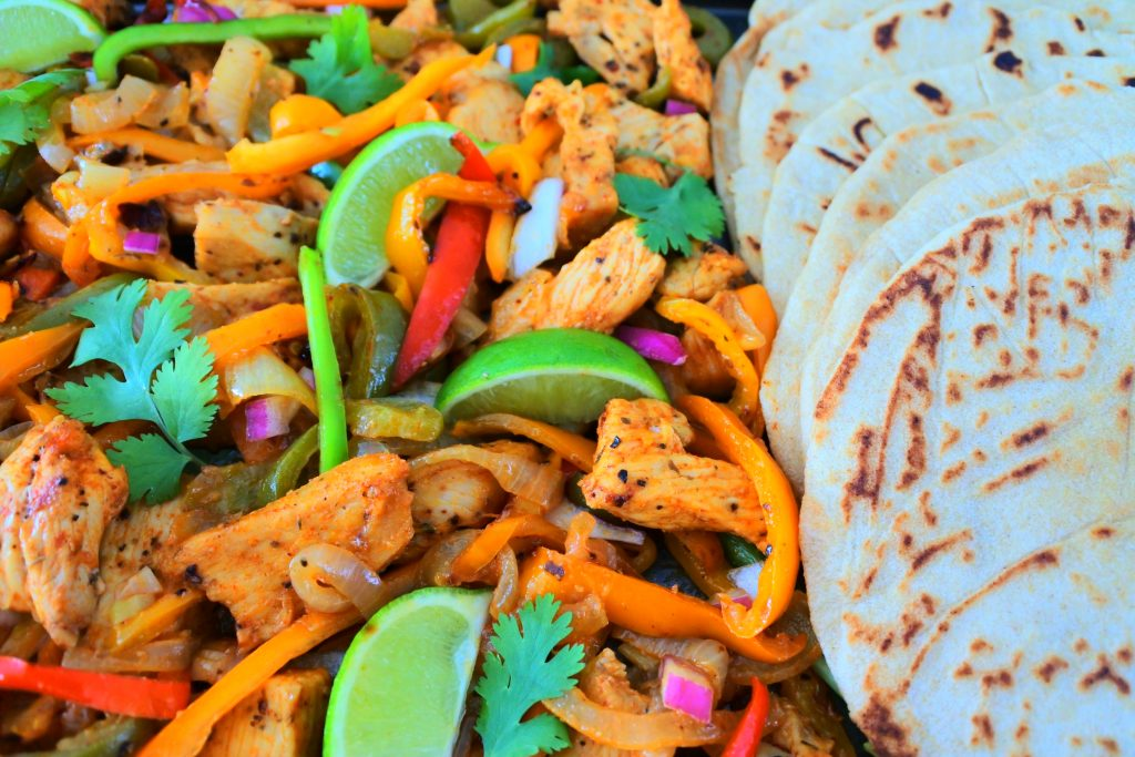 A close up image of cooked chicken fajitas next to a row of soft and fluffy whole wheat tortillas