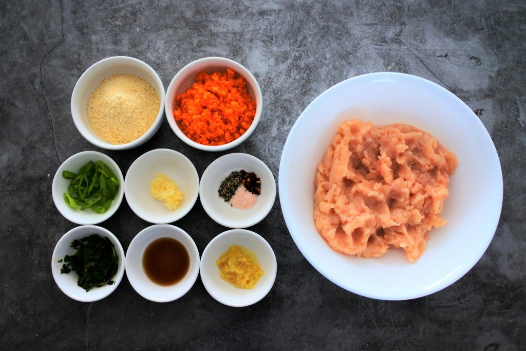 An overhead view of bowls of ingredients for Thai Chicken Meatballs including ground chicken, diced carrots, almond flour, sliced chives, grated garlic, salt, pepper, red pepper flakes, fresh cilantro, fish sauce, and grated ginger