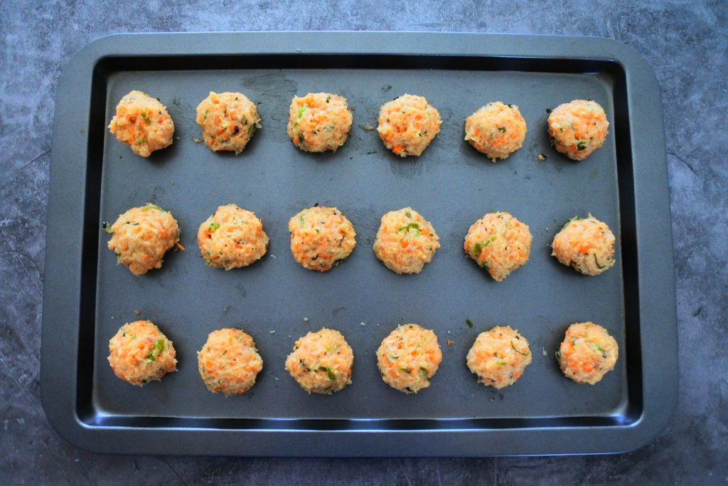 An overhead view of unbaked Thai Chicken Meatballs on a baking tray