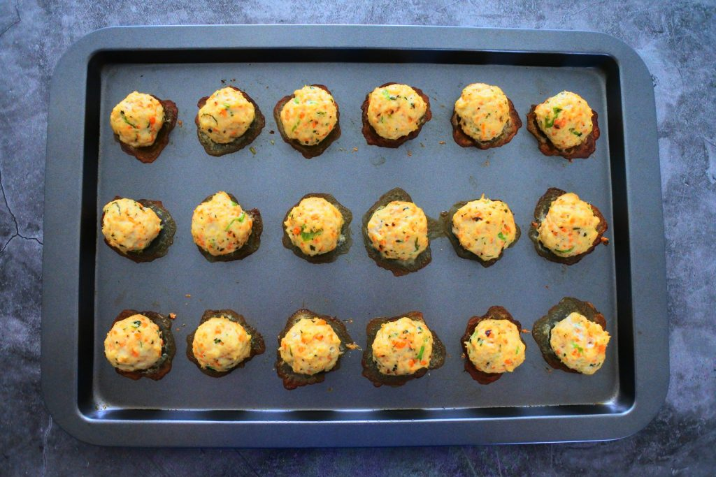 An overhead view of baked Thai Chicken Meatballs on a baking tray
