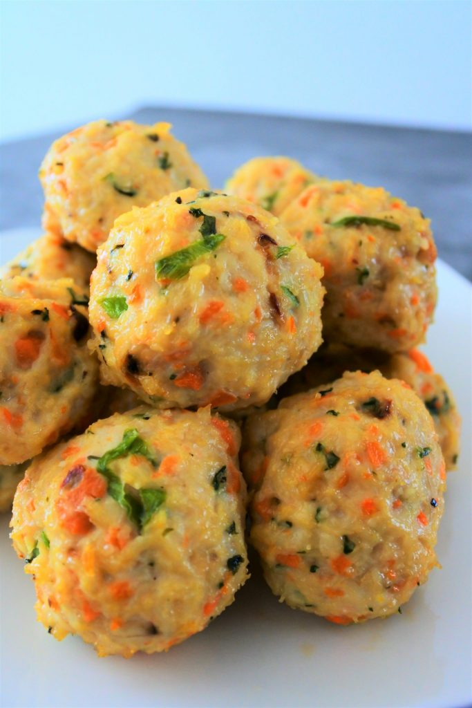 A head on close up image of a pile of baked thai chicken meatballs on a plate.