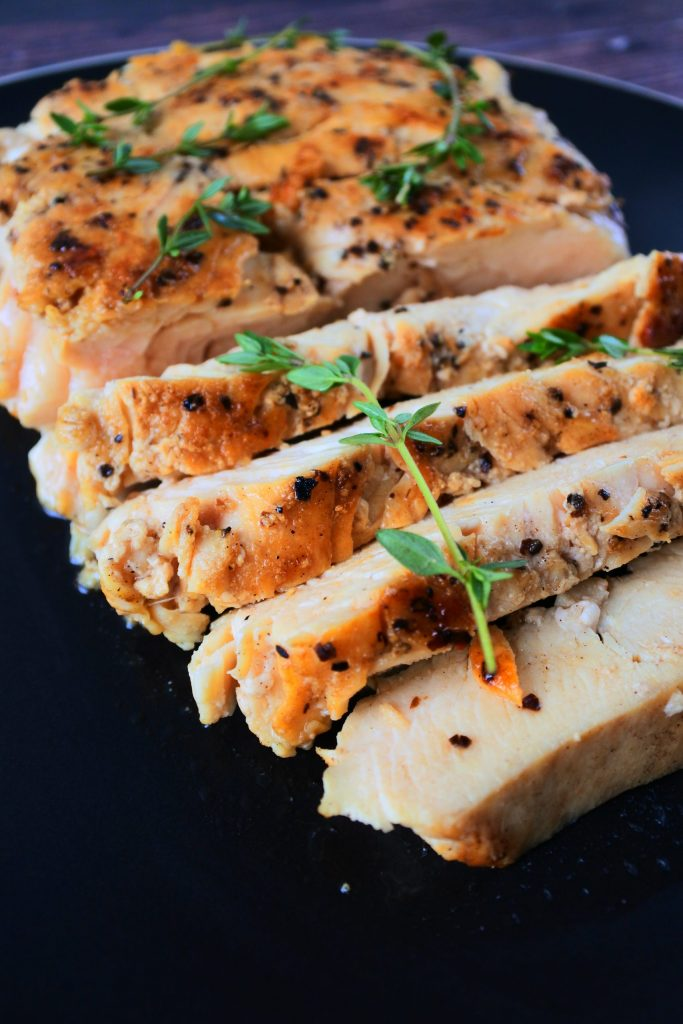 A close up image of sliced pan seared chicken breast topped with fresh thyme sprigs