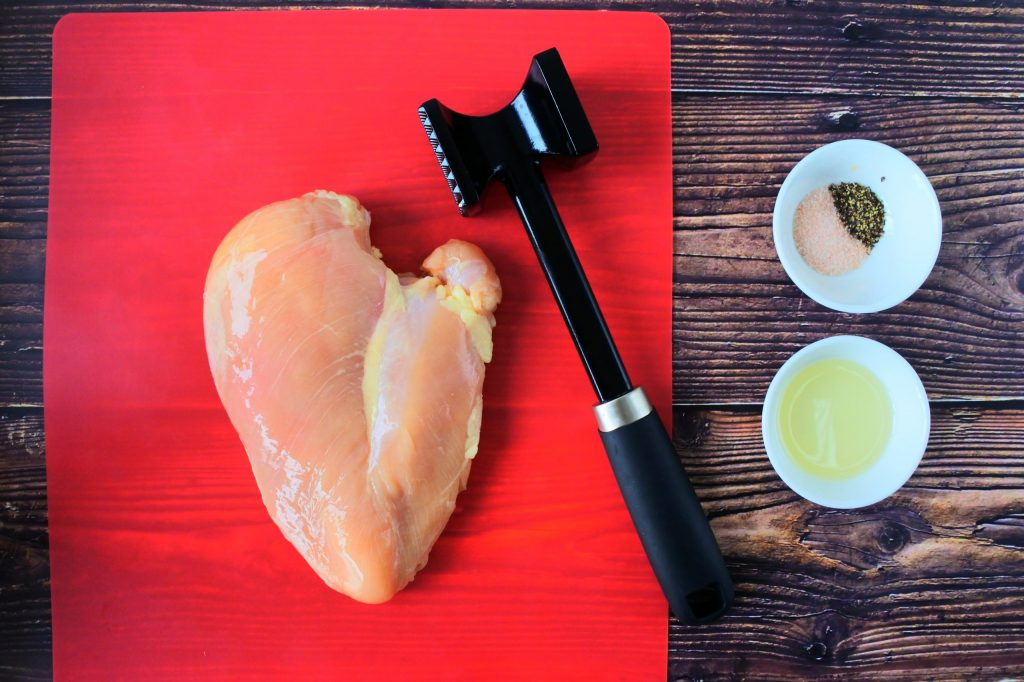 An overhead image of a raw chicken breast on a cutting mat next to a meat mallet with two small dishes of oil and salt and pepper on the side.