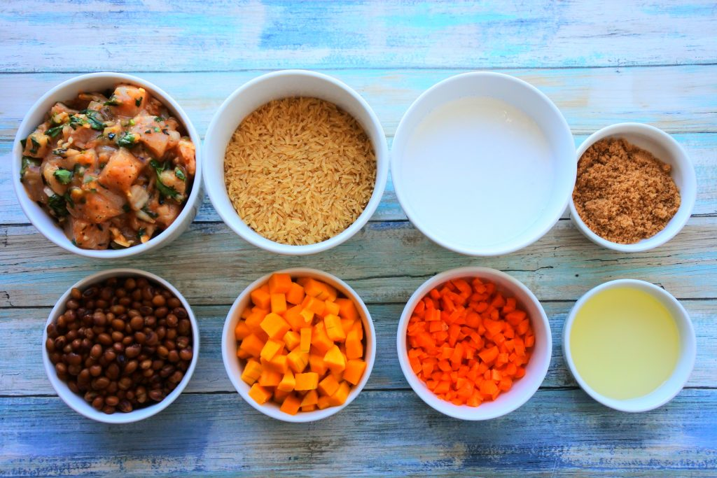 An overhead image of bowls containing ingredients for pelau including seasoned cubed chicken, rice, coconut milk, raw brown sugar, pigeon peas, cubed squash, diced carrots and light olive oil