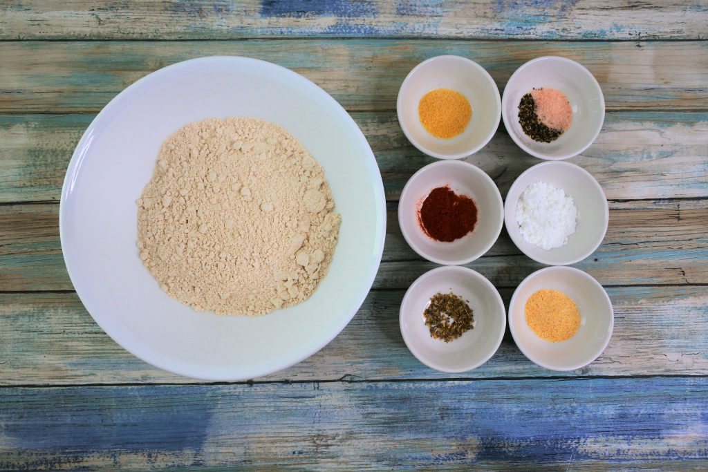 An overhead image of bowls containing Stone Ground 100% Whole Wheat Pastry Flour, garlic powder, smoked paprika, cayenne pepper, dried oregano, salt and pepper, baking powder and onion powder.