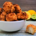 A close up image of a bowl of popcorn chicken with some lemons and limes in the background