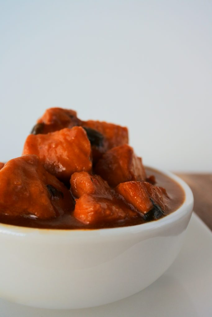 A head on image of a bowl of Caribbean-style stew chicken swimming in a rich caramelized gravy/sauce