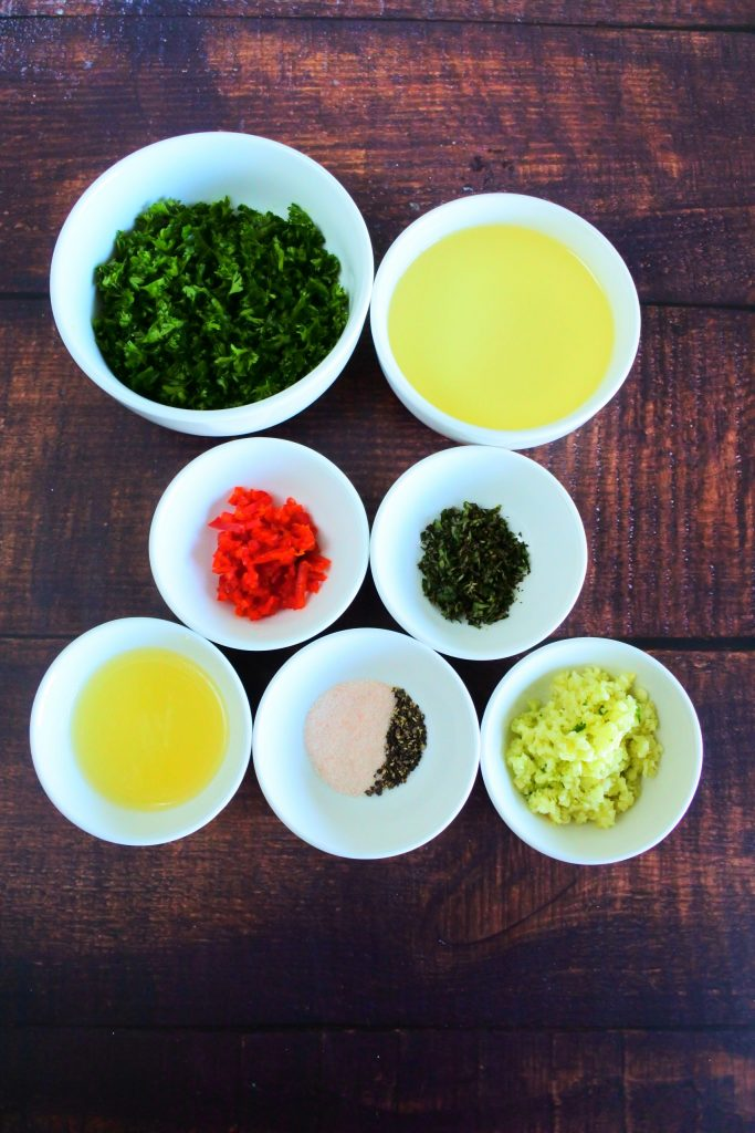 An angled image of bowls of ingredients for a chimichurri sauce including freshly chopped parsley, olive oil, finely diced red chili, finely chopped oregano, fresh lemon juice, salt and pepper and finely minced garlic