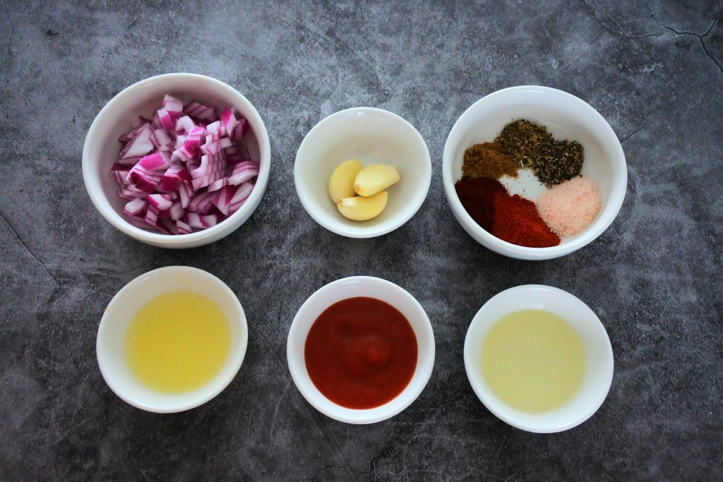 An overhead image of bowls of ingredients for chipotle chicken including diced red onions, garlic cloves, a bowl of various spices, lemon juice, tomato sauce and light olive oil