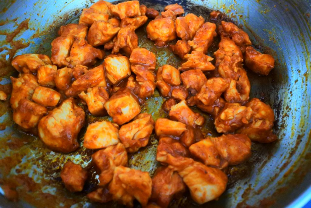 A close up image of a skillet of chipotle chicken pieces being cooked