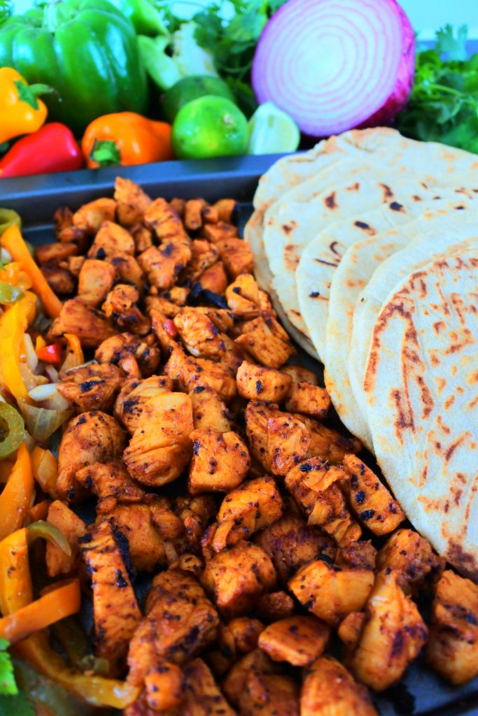 An angled vertical image of a tray of fajita vegetables, blackened chipotle chicken, and whole wheat flour tortillas, with fresh herbs and vegetables in the top border