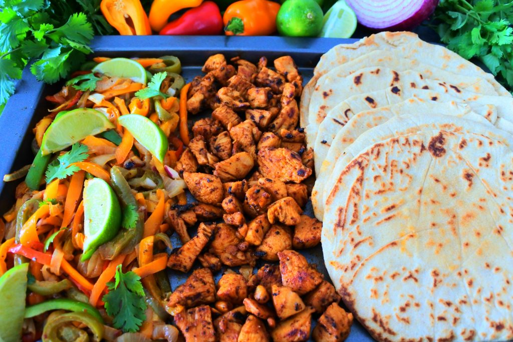An angled overhead image of a tray of fajita vegetables, blackened chipotle chicken, and whole wheat flour tortillas, with fresh herbs and vegetables in the top border