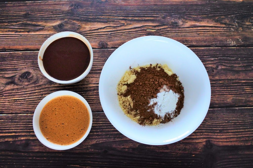 An overhead image of three bowls, one containing uncombined dry ingredients including almond flour, cocoa powder, salt and baking powder, another bowl containing a ,ix of melted chocolate and coconut oil, and the third containing a blend of eggs and coconut sugar