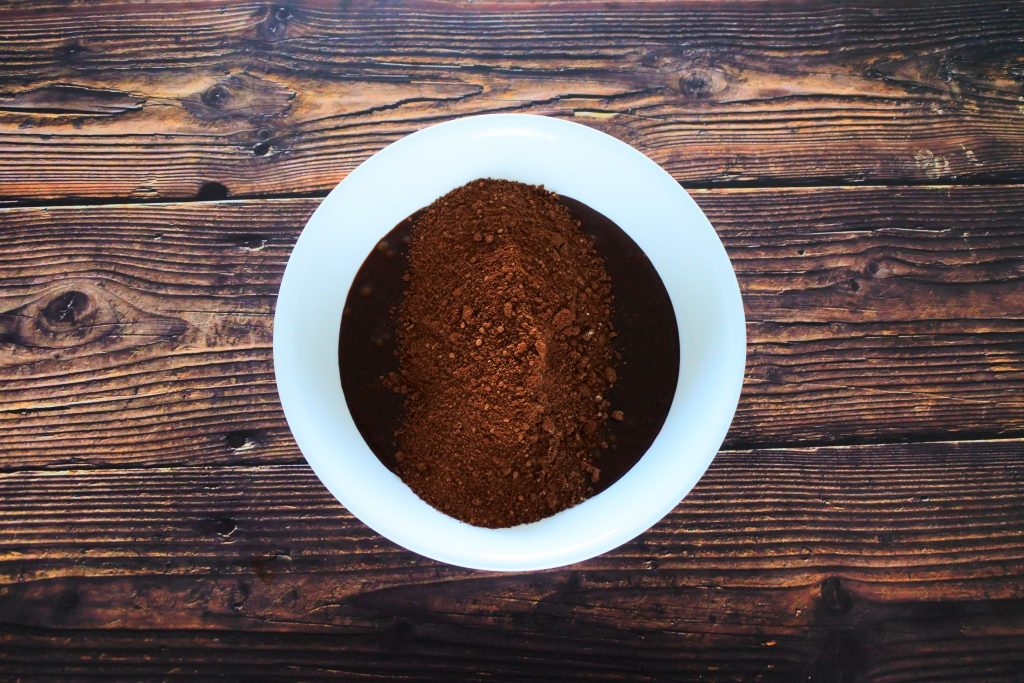 An overhead image of a bowl of unmixed brownie batter ingredients