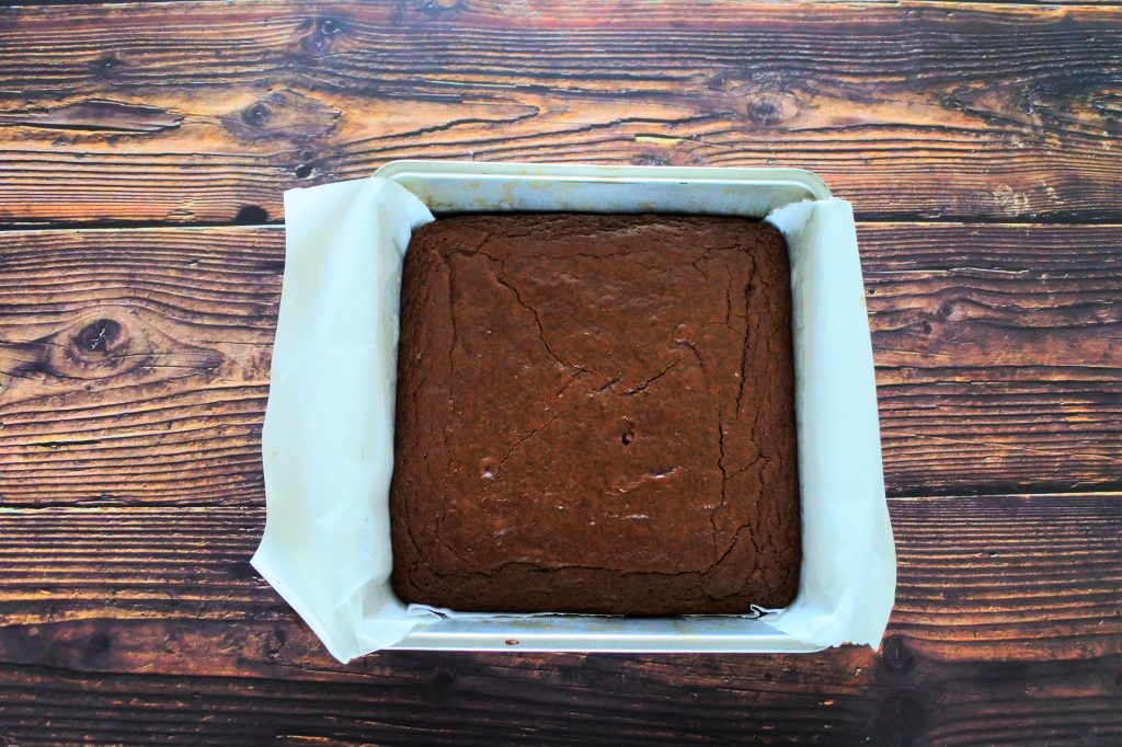 An overhead image of a square metal tin lined with parchment paper and filled with freshly baked, uncut brownies