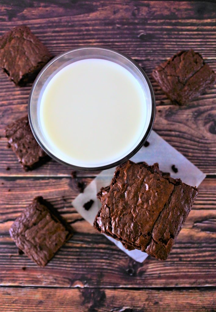 Am overhead image of a glass of milk and a tower of brownies surrounded by squares of brownies on a wooden tabletop