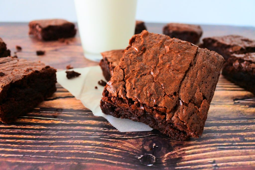 A close up image of a square of brownie on a piece of parchment paper with other brownies and a glass of milk in the background