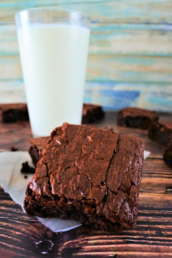 A close up of an angled square of brownie with a glass of milk in the background