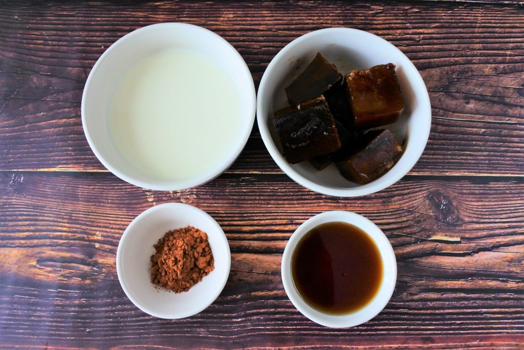 An overhead image of bowls of ingredients for a blended iced coffee frappe including coffee ice cubes, milk, maple syrup and cocoa powder