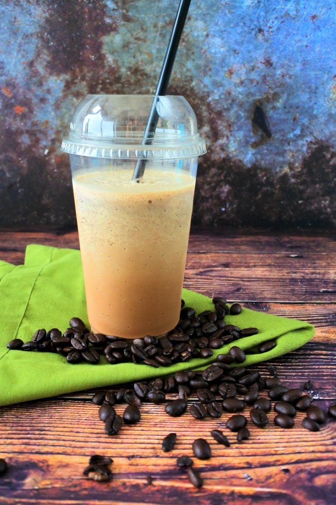 A head on image of a blended iced coffee frappe with a black straw on a green linen napkin surrounded by coffee beans.
