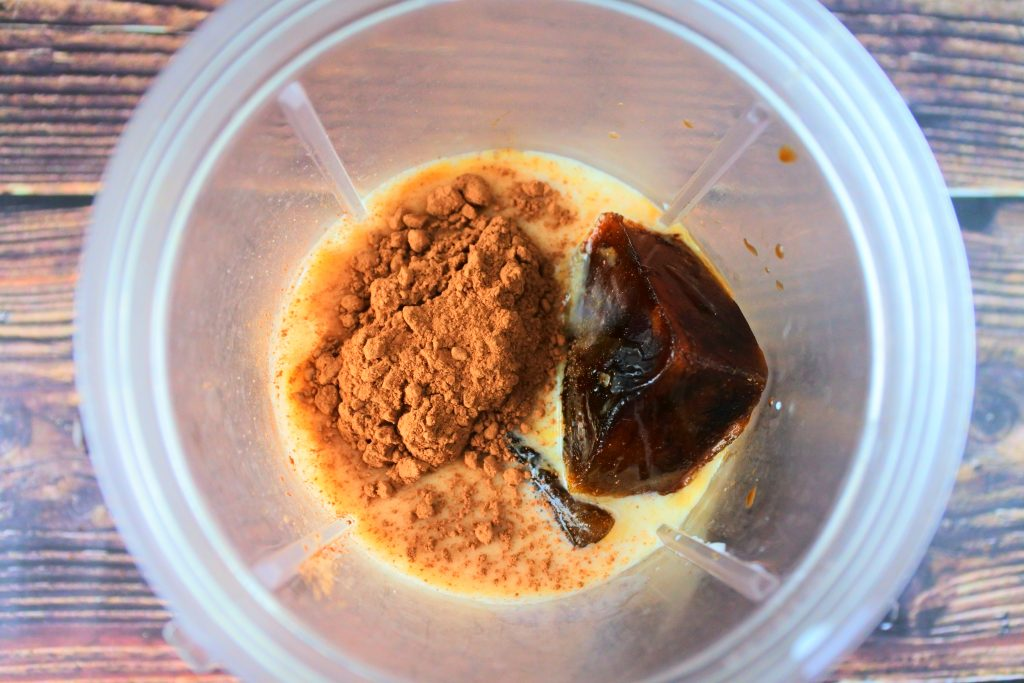 An overhead image of ingredients for a blended iced coffee frappe in a cup including milk, coffee ice cubes and cocoa powder