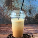A head on image of a blended iced coffee frappe with a black straw surrounded by coffee beans.