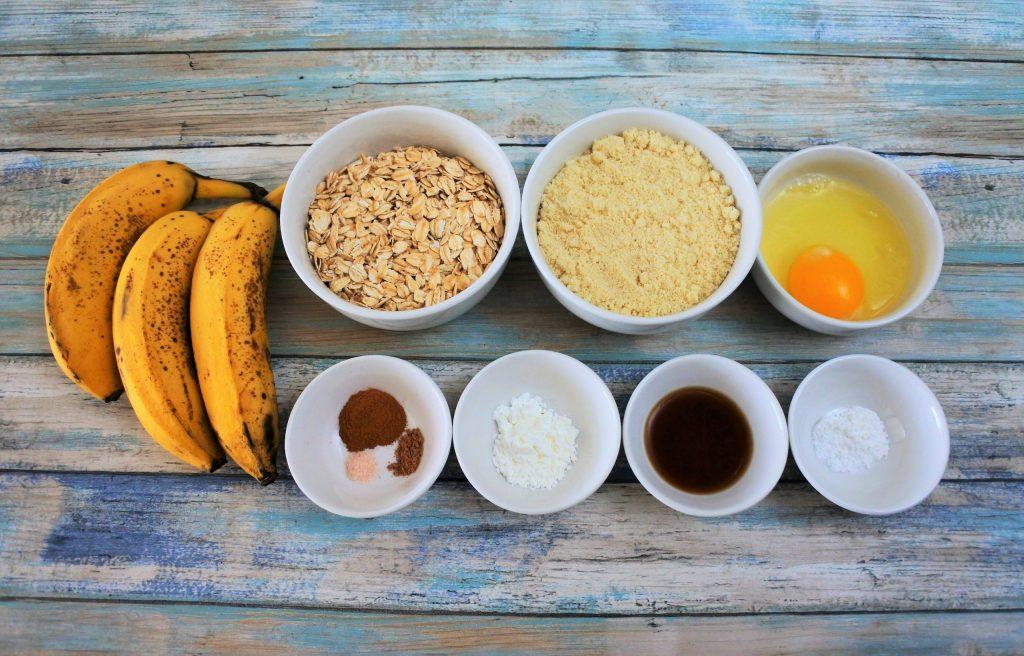 An overhead image of ingredients for banana oatmeal cookies including ripe bananas, rolled oats, almond flour, an egg, baking powder, vanilla, tapioca flour, and salt, nutmeg and cinnamon