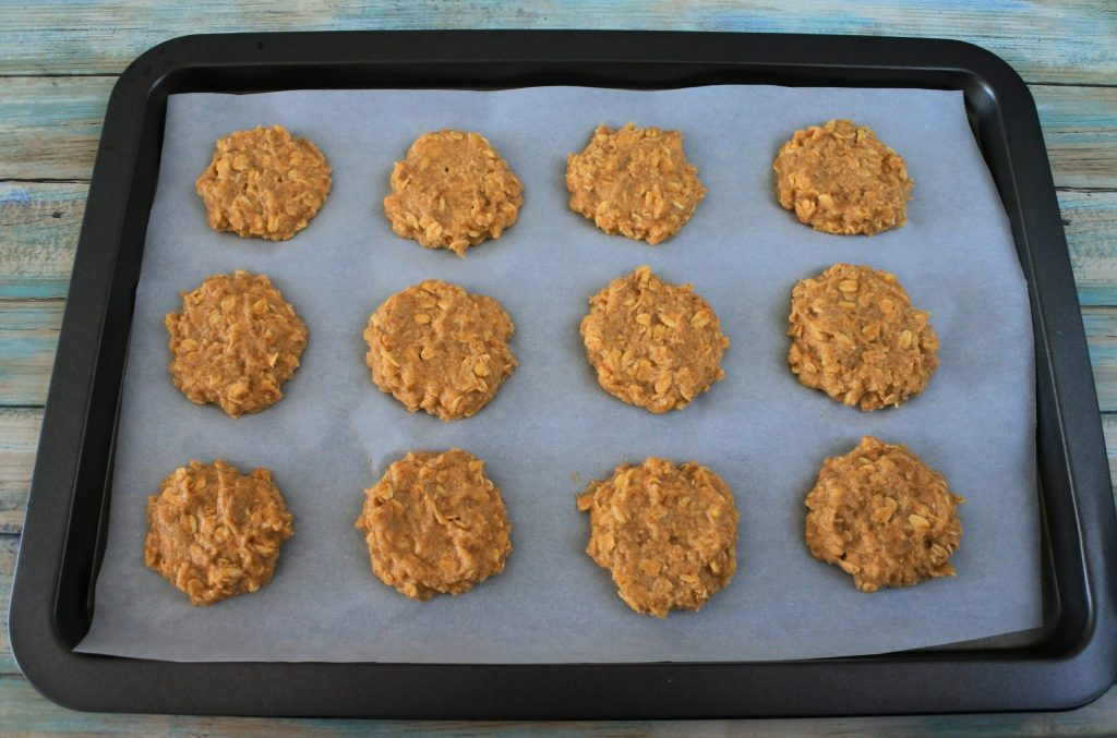 An angled image of a parchment-lined baking tray with unbaked banana oatmeal cookies on it