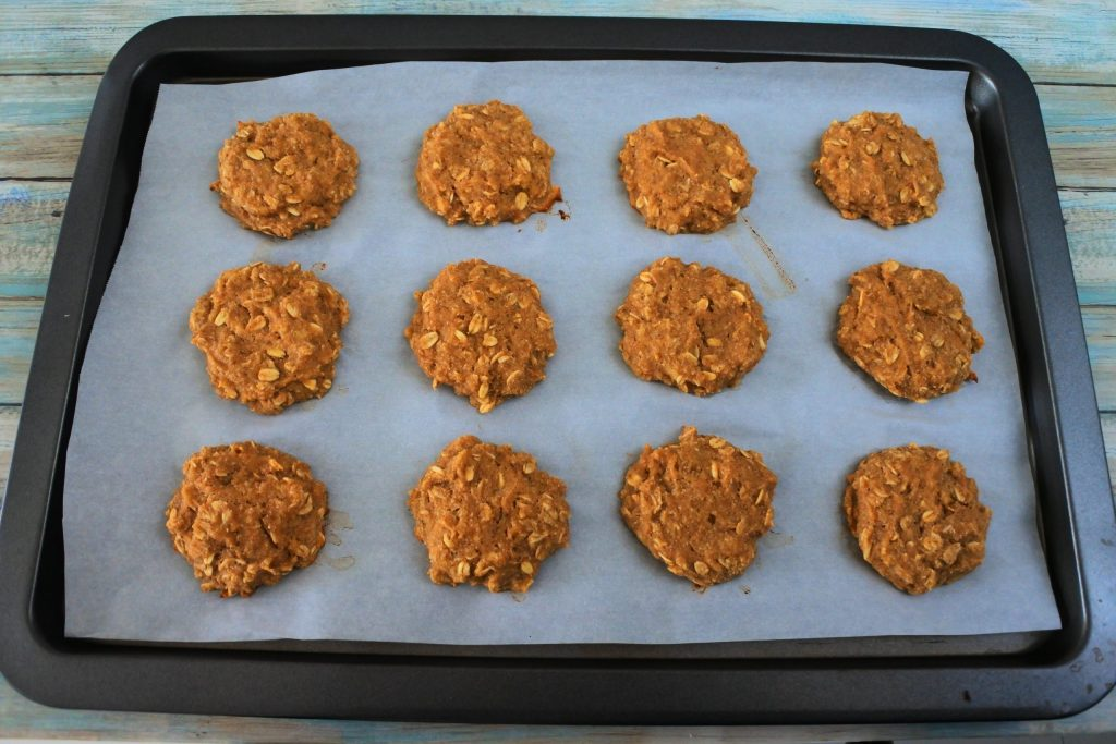 An angled image of a parchment-lined baking tray with baked banana oatmeal cookies on it