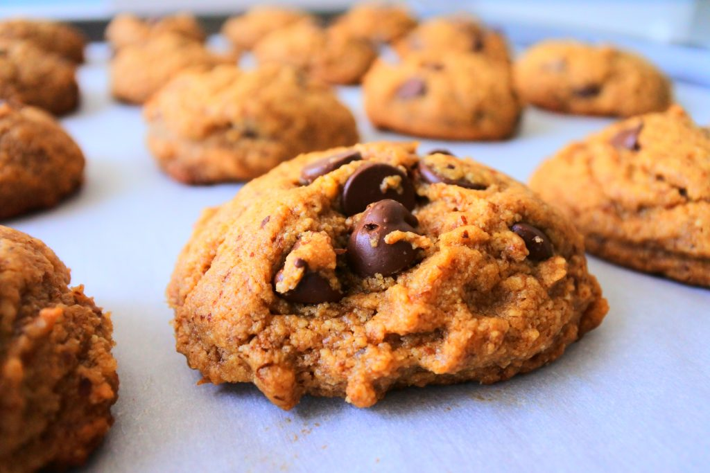 A head-on close up image of a chocolate chip cookie on a tray with a background of out-of-focus chocolate chip cookies