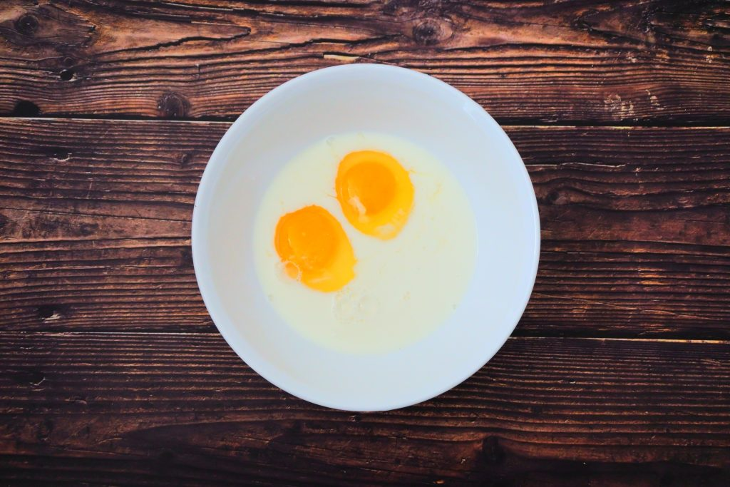 An overhead image of two cracked eggs in a bowl with some milk