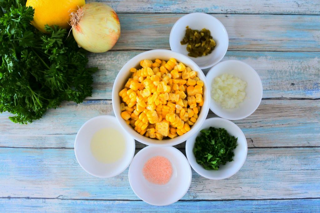 An overhead of bowls of ingredients for corn salsa including fresh corn, jalapeno, onion, cilantro and parsley, salt and lemon juice