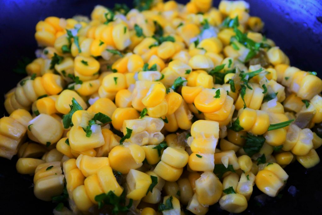 Close up image of corn tossed with spices and herbs for a corn salsa