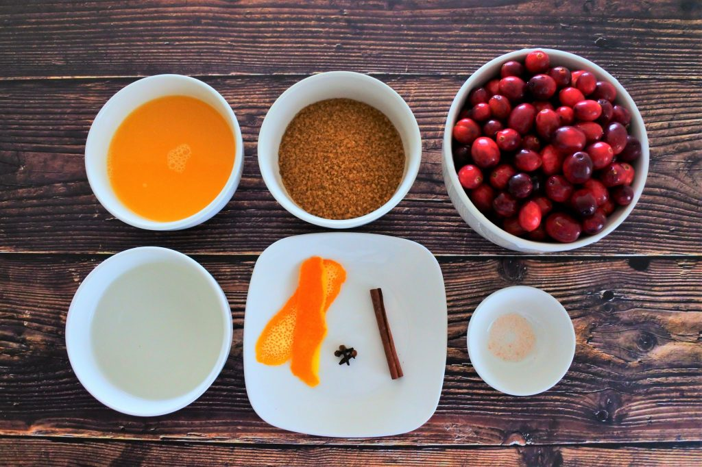 An overhead image of ingredients for homemade cranberry sauce including freshly squeezed orange juice, raw cane sugar, fresh cranberries, water, orange peel, whole cloves, a stick of cinnamon and salt.