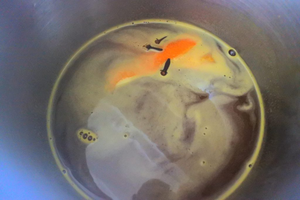 An overhead image of a pot with orange juice, with cloves and orange peel floating on the surface