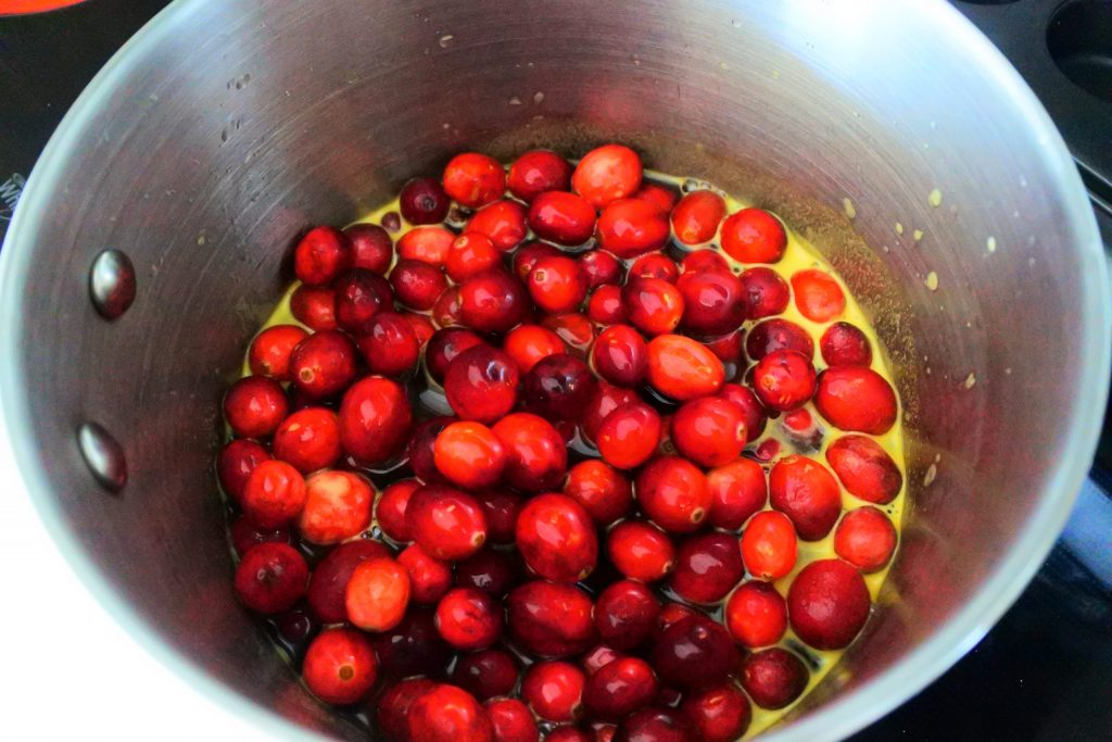 An angled overhead image of a pot with fresh cranberries in a spiced and sweetened orange juice