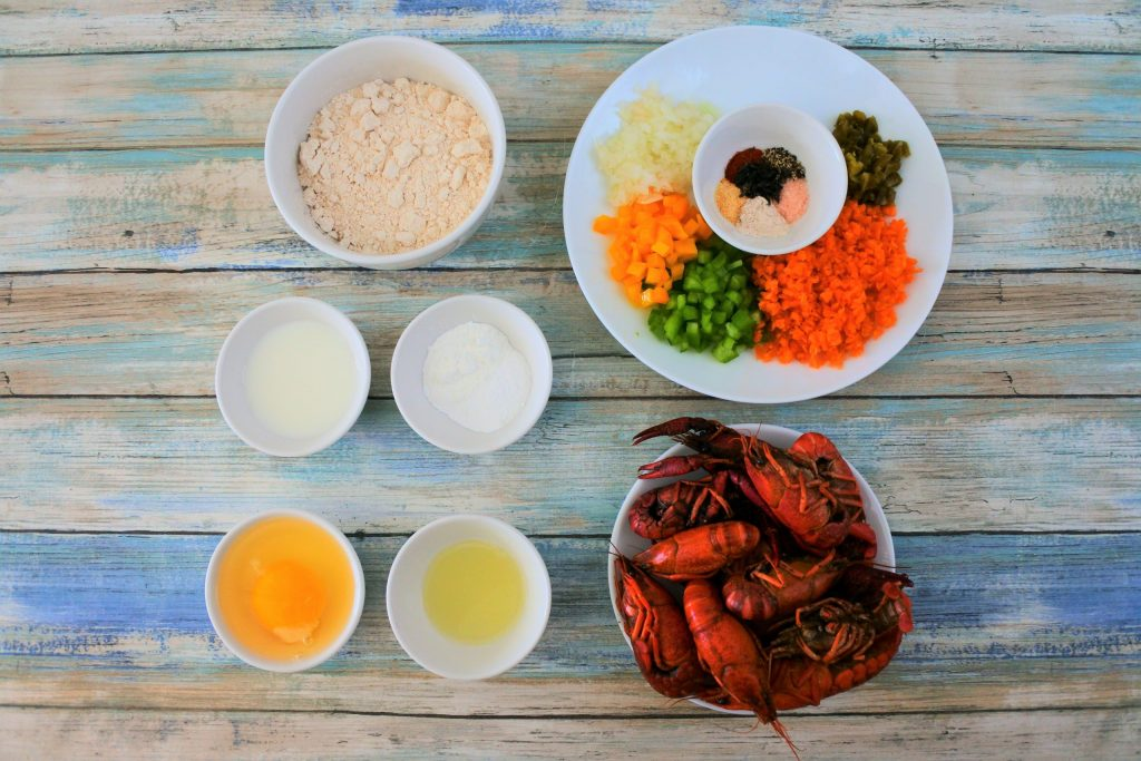 An overhead image of ingredients needed for crawfish fritters including whole wheat pastry flour, milk, potato starch, baking powder, egg, lemon juice, crawfish, and various other herbs and spices
