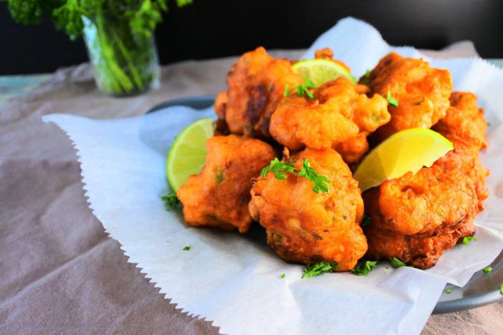 A close up image of a plate of crawfish fritters garnished with parsley and lime wedges.