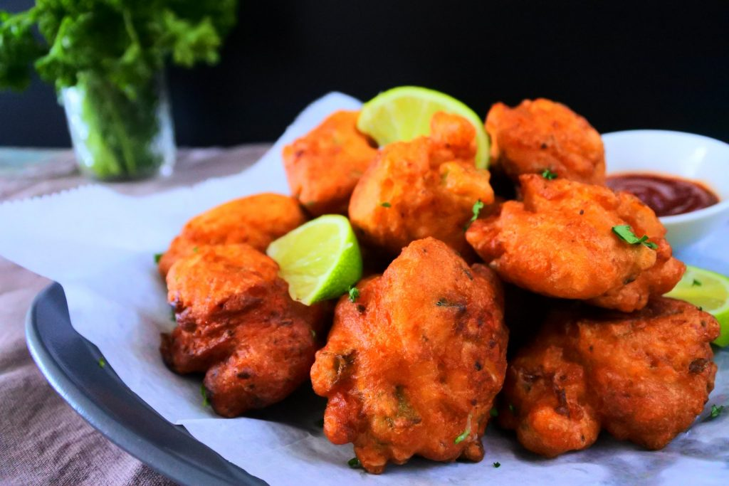 A close up image of a plate of crawfish fritters garnished with parsley and lime wedges with a small dish of ketchup on the side