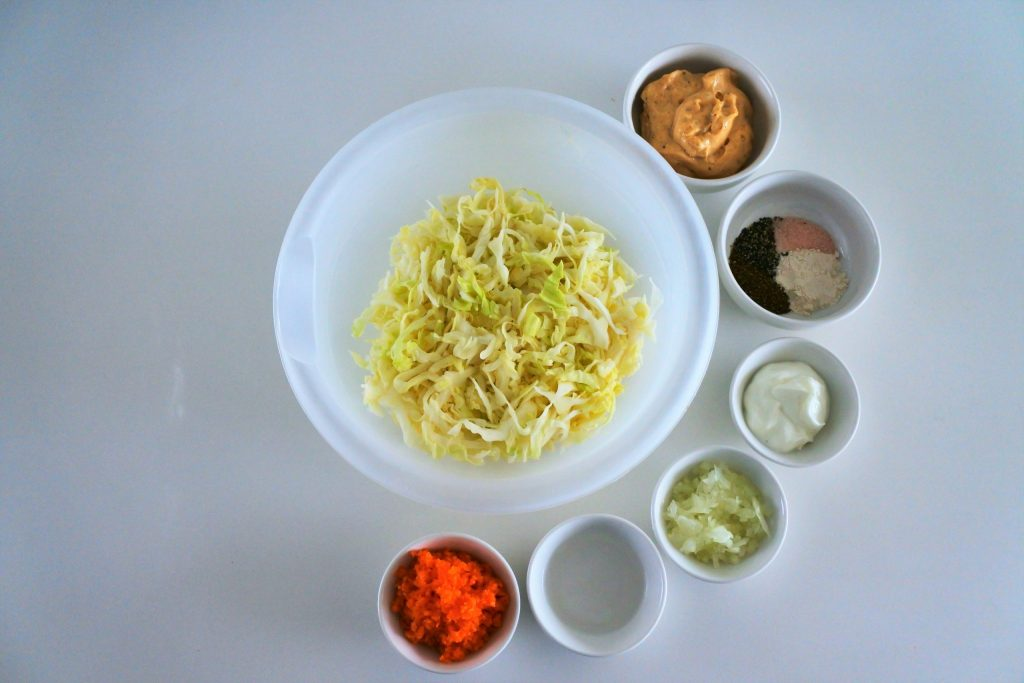 Ingredients for a creamy coleslaw in bowl. They include shredded cabbage, homemade mayonnaise, spices, greek yogurt, minced onion, distilled vinegar, and diced cabbage