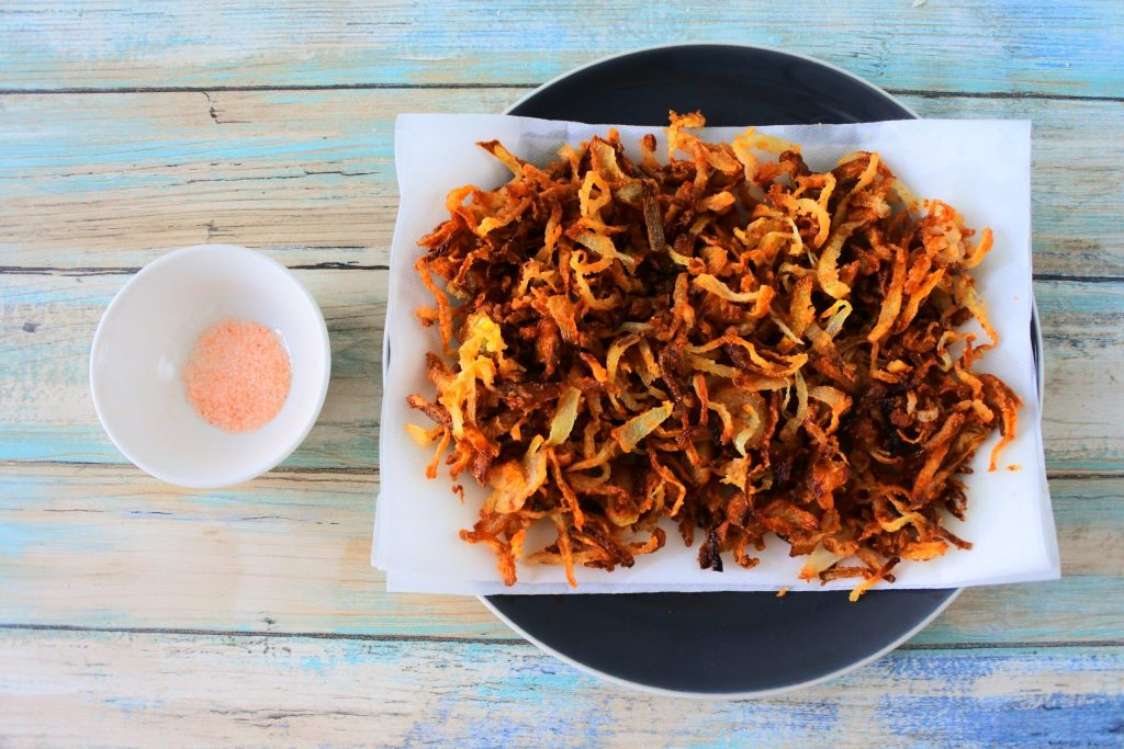 An overhead image of crispy fried onions on a plate with paper towels next to a small dish of salt