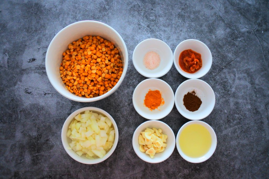 An overhead image of a bowl of split peas, onions, salt, saffron, garlic, oil, roasted cumin and ground pimento peppers